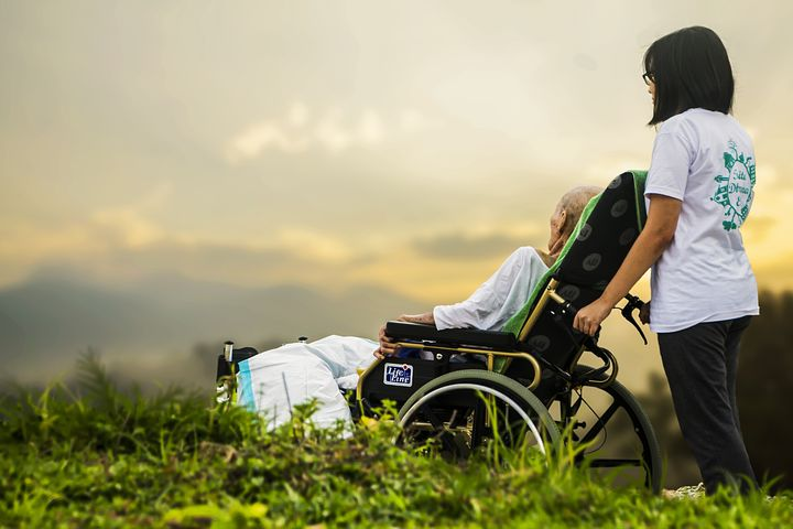 woman assisting an old person in a wheelchair